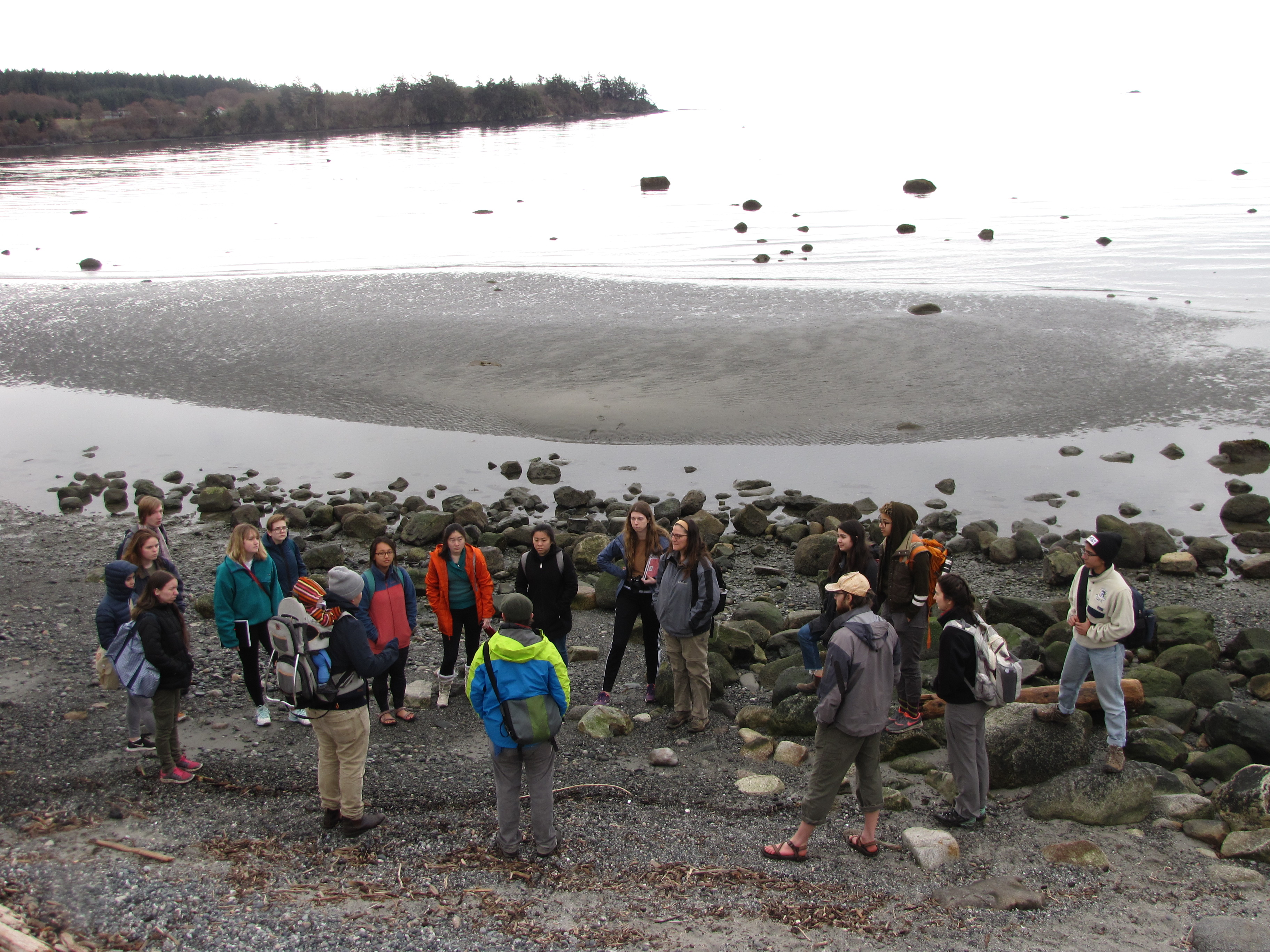 Students gathered on a sandy beach with calm water behind them.