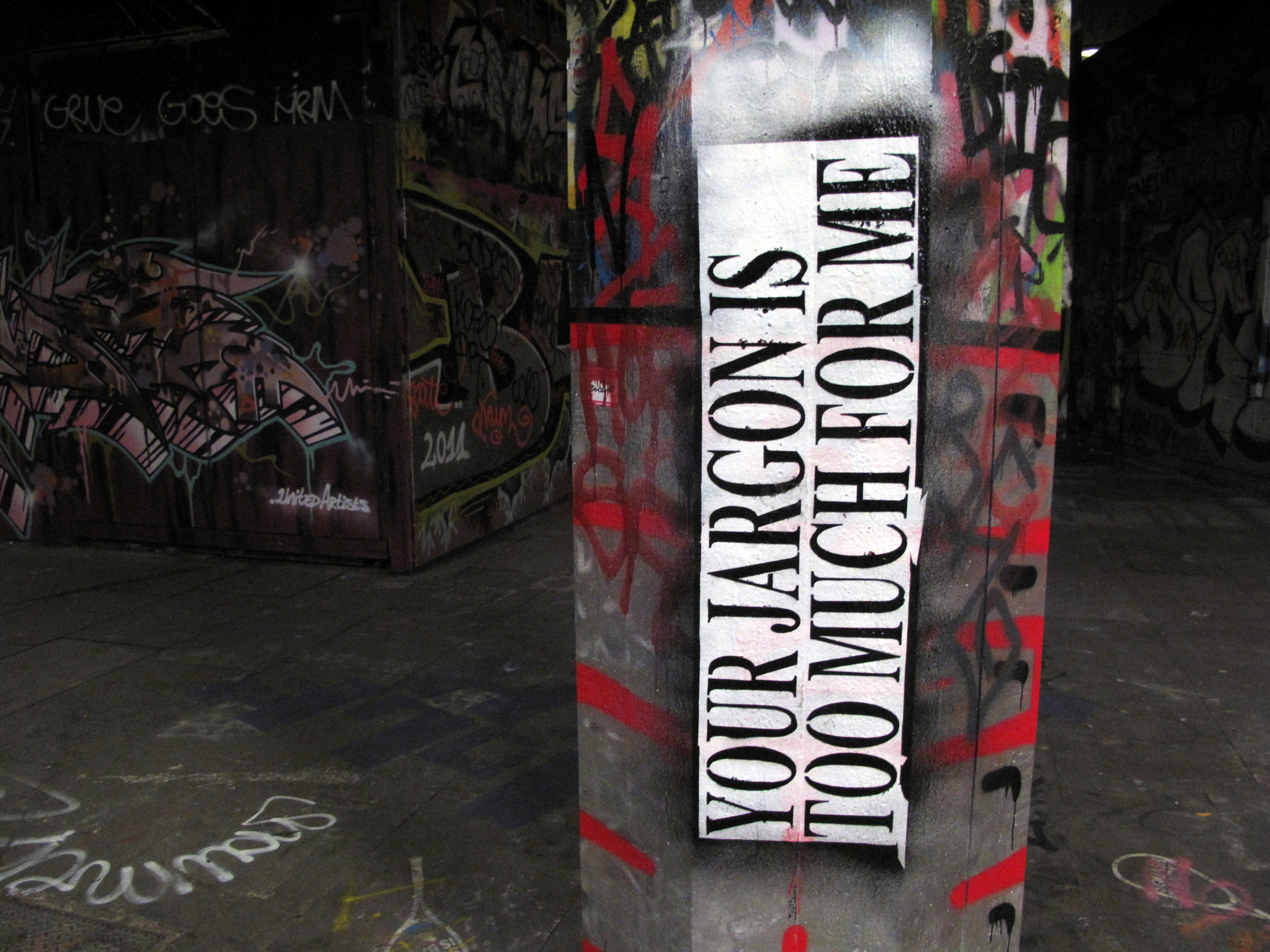 "cement pillar with graffiti text. Text says ""your jargon is too much for me""."