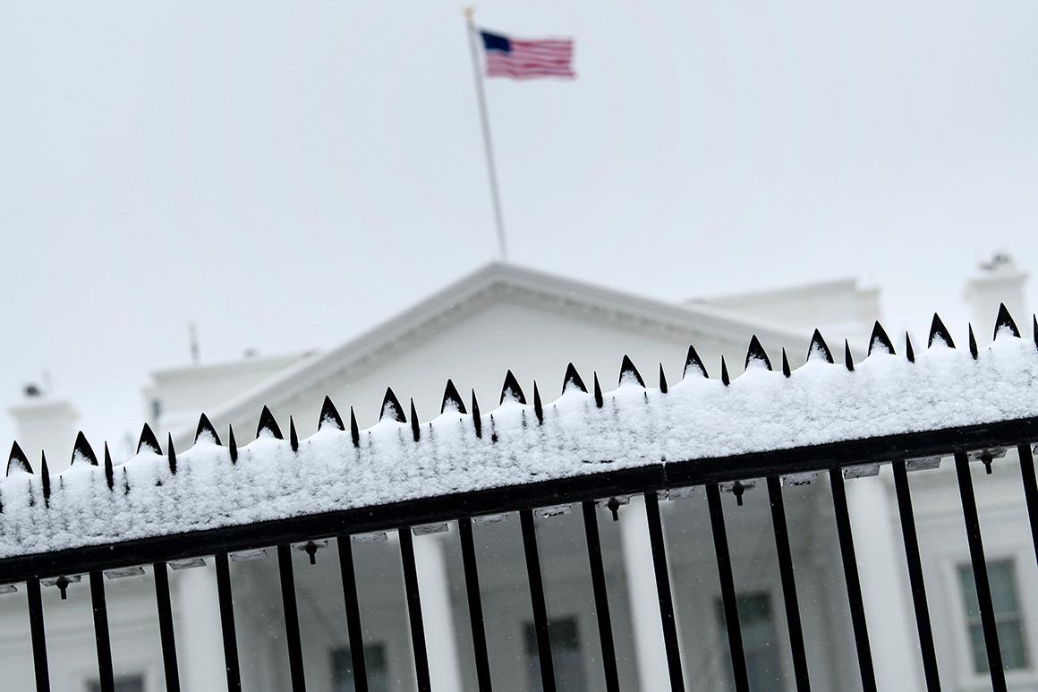 Angled shot of White house through black metal fence