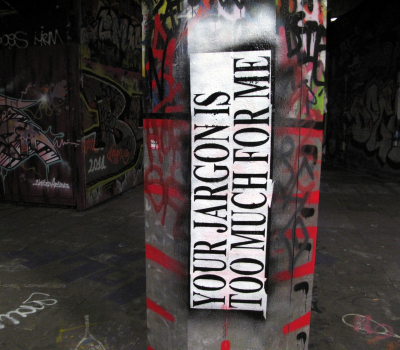 """cement pillar with graffiti text. Text says """"your jargon is too much for me""""."""