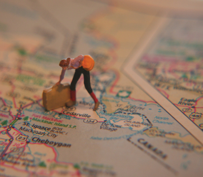 Figuring with briefcase standing on printed map