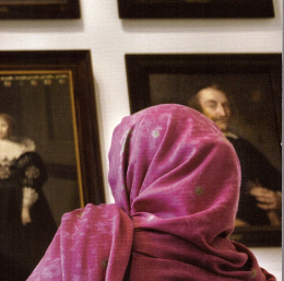 Woman in colorful headscarf in front of somber 17th-century portraits of Dutch elite