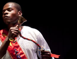 A man in colorful clothes performing with bells in a dark room
