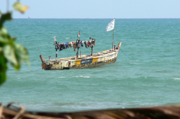 a solitary fishing boat on the ocean in Ghana