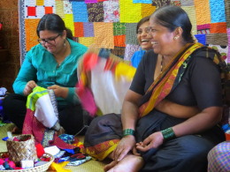 women weaving colorful fabrics and laughing together