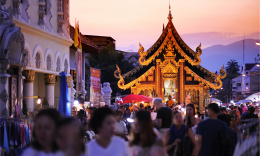 An image of a Buddhist ceremony attended by many people in a beautiful Thai courtyard at dusk.