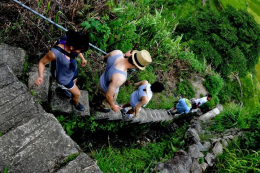 Students hiking down steep steps down the hillside of a rice paddy in the Philippines