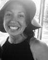 Profile Picture of Lydia Heberling. A black and white photo with Lydia wearing a soft brim sun hat and black sleeveless top.