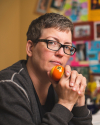 A portrait of Jen Self contemplating a billiard ball in a colorful office