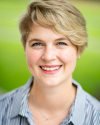 Torie Reed's Profile Picture: Close up portrait with green background. Torie is smiling while wearing a blue striped shirt.