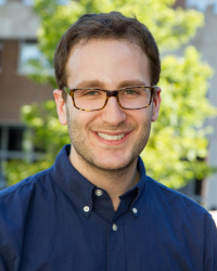 Profile Picture of Daniel Bessner: He has short brown hair, wire frame glasses and is wearing a blue button up shirt.