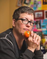 A portrait of Jen Self contemplating a billiard ball in a colorful office
