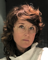 a person with brown hair, glasses, in a white turtle neck