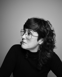 a person with brown hair, glasses, in a black turtle neck