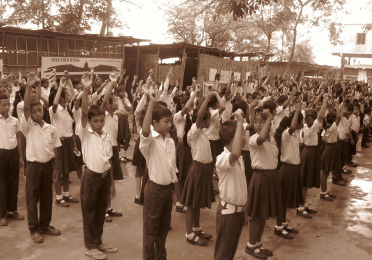 Sepia toned image of South Asian primary school students lining up.