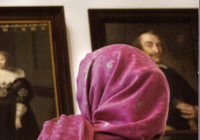 A woman in a headscarf views portraits in a Dutch museum