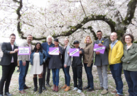 "A group portrait of Comparative History of Ideas faculty and staff beneath cherry blossoms in the quad, holding signs that say, ""question. critique. create."""