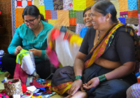 three women weaving colorful fabrics