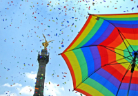 Rainbow flag umbrella in front of tower