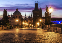 An image of a beautifully lit Prague street overlooking monuments and castles at dusk
