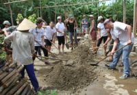 Students and locals in a circle working together with shovels