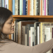 Alyssa Taylor reaching to grab a library book from a packed shelf